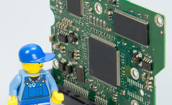 Płytka elektroniczna ze stojącym obok ludzikiem LEGO w stroju elektryka